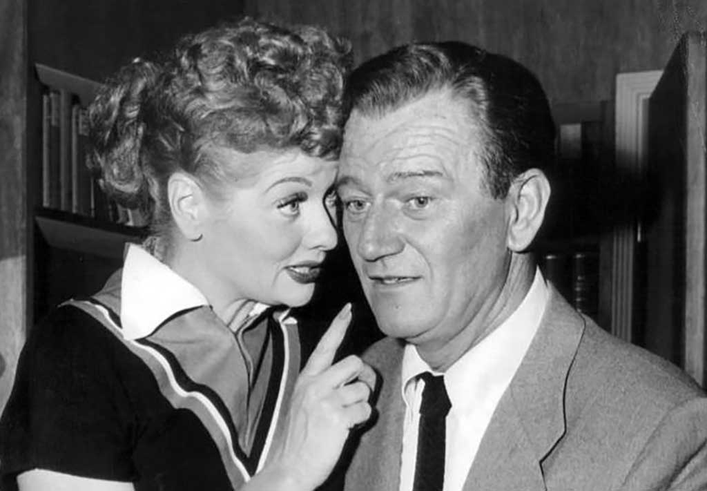 Lucille Ball pitches a show idea to John Wayne (1955). Wikimedia Commons public domain image